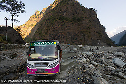 A tourist bus heads through a water crossing in the Himalayas of Nepal. On the sixth day of riding, we went from Tatopani to Pokhara. Saturday, November 9, 2019. Photography ©2019 Michael Lichter.