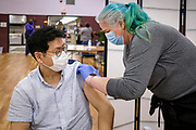 27 MARCH 2021 - DES MOINES, IOWA: MICHAEL CHO gets a COVID-19 vaccination from a volunteer during a COVID-19 (Coronavirus) vaccination clinic at Corinthian Baptist Church in Des Moines, Saturday. The clinic was organized by Broadlawns Medical Center and the United Way and provided more than 1,100 shots to Des Moines area residents. The clinic was a part of an effort to reach communities of color in Iowa, who are vaccinated at rates below the state average.       PHOTO BY JACK KURTZ