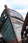 Disused rusty derelict blue fishing boats at Salen Bay in Sound of Mull on Isle of Mull in the Inner Hebrides and Western Isles, West Coast of Scotland