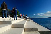Tourists gather at the award-winning Sea Organ (morske orgulje). Zadar, Croatia