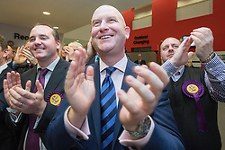 © Licensed to London News Pictures . 10/10/2014 . Heywood , UK . UKIP supporters (centre Paul Nuttall ) cheer as the declaration at the Clacton count is broadcast on TV . The count at the Heywood and Middleton by-election , following the death of sitting MP Jim Dobbin . Photo credit : Joel Goodman/LNP