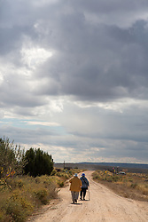 two elderly people walking on a dirt road in New Mexico