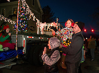 Families lining the parade route greeted Santa and Mrs. Claus during Sunday's annual holiday parade and tree lighting in downtown Laconia.  (Karen Bobotas/for the Laconia Daily Sun)