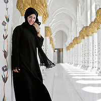 Abu Dhabi, United Arab Emirates 07 April 2009.AN Emirati woman poses for the photographer inside the Sheikh Zayed Mosque..Sheikh Zayed Mosque in Abu Dhabi is the largest mosque in the United Arab Emirates and the sixth largest mosque in the world. .It is named after Sheikh Zayed bin Sultan Al Nahyan, the founder and the first President of the United Arab Emirates, who is also buried there. The Mosque is large enough to accommodate 40,000 worshippers. The main prayer hall can accommodate up to 9,000 worshippers. Two rooms next to the main prayer hall, with a 1,500-capacity each, are for the exclusive use of women..PHOTO: EZEQUIEL SCAGNETTI