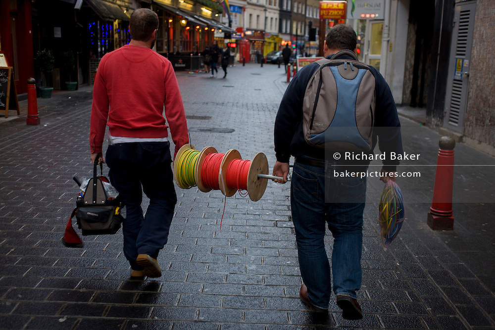 Workmen carry a spool of wiring through a Soho street in London's West End.