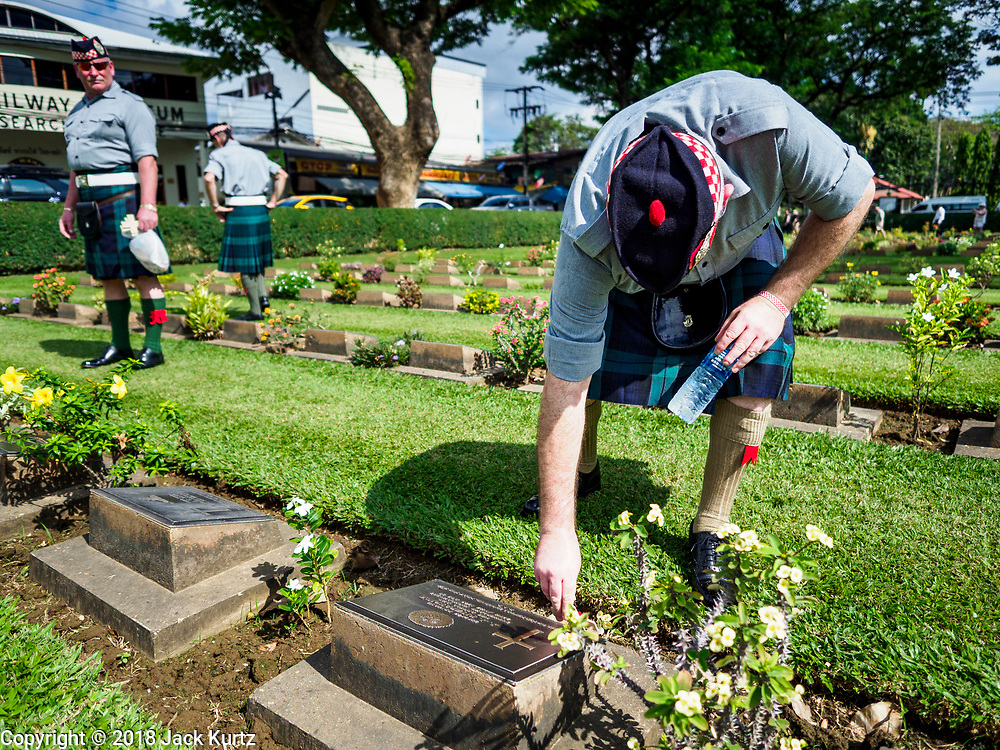 "11 NOVEMBER 2018 - KANCHANABURI, KANCHANABURI, THAILAND: STEWART WILSON, a Scottish veteran of the British army, leaves a cross on the grave of a Scottish soldier killed on the ""Death Railway"" during the Rememberance Day ceremony at the Kanchanaburi War Cemetery in Kanchanaburi, Thailand. Kanchanaburi is the location of the infamous ""Bridge On the River Kwai"" and was known for the ""Death Railway"" built by Japan during World War II using allied, principally British, Australian and Dutch, prisoners of war as slave labor. There are 6,982 people buried in the cemetery, including 5,000 Commonwealth soldiers and 1,800 Dutch soldiers. November 11, 2018 marked the 100th anniversary of the end of World War I, celebrated as Rememberance Day in the UK and the Commonwealth and Veterans' Day in the US.     PHOTO BY JACK KURTZ"