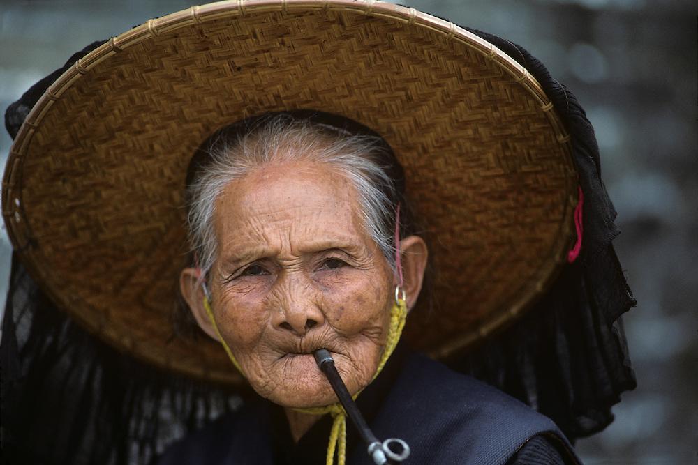 China, Hong Kong, Old woman smokes pipe while wearing traditional Hakah clothing in walled village of Kam Tin