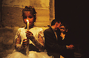 """Europe, France, Camargue, Saintes Maries de la Mer. A Roma Gypsy girl with a candle awaits  her christening, in a church. The Gypsy festival """"le Pelerinage des Gitans aux Saintes Maries de la Mer"""" takes place every year in mid May. Gypsies arrive from all over Europe a few weeks before the main festival days, the 24th and 25th May.  The pilgrimmage is Catholic but many Gypsies, Manouche, Gitans, Roma come to see their patron 'Saint Sara' and for the festival atmosphere, the yearly gathering of friends, the music and dance. Gypsies are still regarded with much distrust and racism, they are not liked by the shopkeepers but are well treated by the gentry, especially the Baroncelli family who were instrumental in making this officially a Gypsy festival. One Hundred years ago the Gypsies were not allowed into the church, as it is they still have to camp outside the town."""