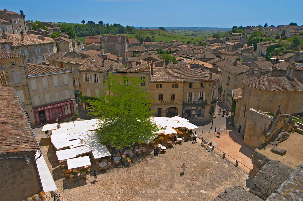 The main town square in Saint Emilion with Cafes with outside seating terrasse with parasols, people drinking and eating in the sun and a view over the whole village with rooftops roof tops and the vineyards in the background Saint Emilion Village Bordeaux Gironde Aquitaine France