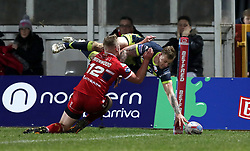 Wakefiekd Trinity's Tom Johnstone (right) dives in to score his sides first try of the game during the Betfred Super League match at Craven Park, Hull.