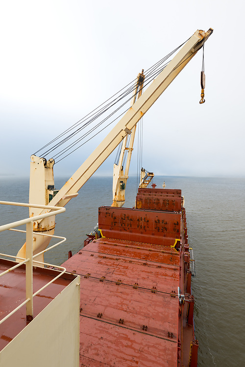 Close-up to te tower cranes and storage hold of a Cargo ship in the Pacific Ocean in the coast of Chile.