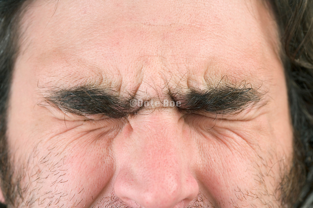 close up of a man's face with his eyes tightly closed