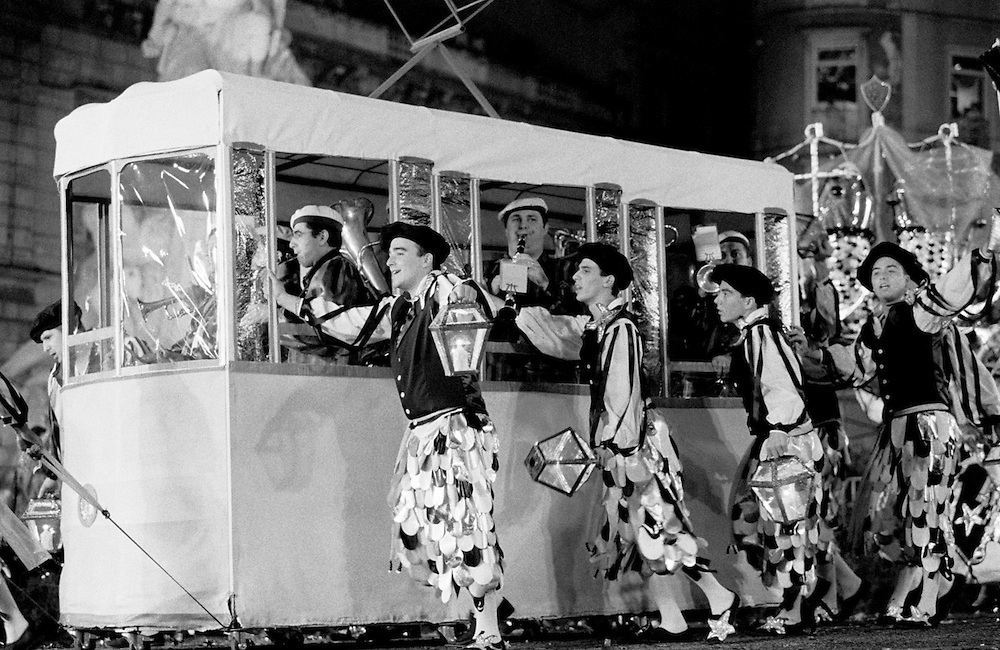 """The Parade in Liberdade Avenue is the climax of months of preparation. Bica neighbourhood march had a replica of the tram that runs in one of its streets. The costumes and music were inspired in traditional fishsellers that used to work in the neighbourhood. Every 12th of June, Lisbon's typical neighbourhoods show their """"marches"""". These consist on music, coreography and costumes inspired on each neighbourhood traditions. The streets of each old Lisbon neighbourhood gets crowded with people partying. The smell of grilled sardines fills the air as people celebrate Saint Anthony's day (13th June), Lisbon's patron saint."""