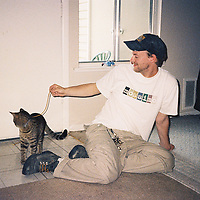 """1. When was this photo taken?<br /> <br /> 2001-2002<br /> <br /> 2. Where was this photo taken?<br /> <br /> Her apartment in suburbs of Balitmore<br /> <br /> 3. Who took this photo?<br /> <br /> An old girlfriend of mine<br /> <br /> 4. What are we looking at here?<br /> <br /> I am playing with her one-year-old cat, named Monster. I am also wearing a pair of Doc Martins that look like hiking boots...woah...<br /> <br /> 5. How does this old photo make you feel?<br /> <br /> Like I was young once!<br /> <br /> This girlfriend of mine eventually became my wife, and our children got to meet this cat. When they saw the photo, they squealed <br /> """"Aaawwwww!""""<br /> <br /> 6. Is this what you expected to see?<br /> <br /> No. I expected a photo from a camping trip, or some family gathering.<br /> <br /> 7. What kind of memories does this photo bring back?<br /> <br /> Apartment living in my early 20s. Roommates, cheap carpet, furniture that doesn't match, linoleum floors...<br /> <br /> 8. How do you think others will respond to this photo?<br /> <br /> They won't care. It's just a guy, playing with a cat, and no one looks particularly great.<br /> <br /> Film photos were uglier. You didn't know what you got, so you didn't take it again if it didn't work out."""