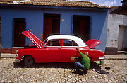 23 JULY 2002 - TRINIDAD, SANCTI SPIRITUS, CUBA: A man works on his car in the colonial city of Trinidad, province of Sancti Spiritus, Cuba, July 23, 2002. Trinidad is one of the oldest cities in Cuba and was founded in 1514..PHOTO BY JACK KURTZ