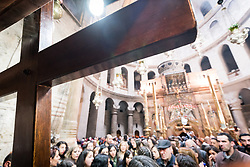 19 April 2019, Jerusalem: Members of the Latin Patriarchate of Jerusalem place a wooden cross into the Church of the Holy Sepluchre. Thousands of Christians march the Via Dolorosa on Good Friday, marking the stations of the cross in the Jerusalem Old City, in memory of the path Jesus walked carrying his cross towards his crucifixion.