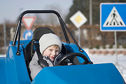 Portrait of boy driving electric toy car