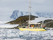 """A hardy yellow sailboat anchors amid sea ice at Vernadsky Research Base (Akademik Vernadsky), a Ukrainian Antarctic Station at Marina Point on Galindez Island in the Argentine Islands, Antarctica. The United Kingdom first established research here as Base F or """"Argentine Islands"""" on Winter Island in 1947, then built a larger hut on Galindez Island in 1954, renamed it Faraday Station in 1977, and shocked the scientific community by discovering the Antarctic """"ozone hole"""" in 1985. The base was transferred to Ukraine in 1996."""