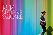 Woman passing a colourful sign for a development at 13-14 Sloane Square, in London. This is situated just off the Kings Road in this most fashionable and wealthy area of London. The square lies at the east end of the trendy Kings Road and at the south end of the more conventionally smart Sloane Street linking to Knightsbridge. In the early 1980s, it lent its name to the 'Sloane Rangers', the young underemployed, often snooty and ostentatiously well-off members of the upper classes.