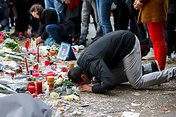 © Licensed to London News Pictures. 16/11/2015. Paris, France. A man praying at a memorial outside Bataclan Cafe in Paris, France following the Paris terror attacks on Monday, 16 November 2015. Photo credit: Tolga Akmen/LNP