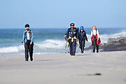 Birders walk on the beach at Saunders Island on Sunday 4 February 2018.