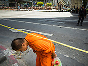 18 AUGUST 2015 - BANGKOK, THAILAND:     A Buddhist monk crosses the street near Erawan Shrine in Bangkok. An explosion at Erawan Shrine, a popular tourist attraction and important religious shrine in the heart of the Bangkok shopping district, killed at least 20 people and injured more than 120 others, including foreign tourists, during the Monday evening rush hour. Twelve of the dead were killed at the scene. Thai police said an Improvised Explosive Device (IED) was detonated at 18.55. Police said the bomb was made of more than six pounds of explosives stuffed in a pipe and wrapped with white cloth. Its destructive radius was estimated at 100 meters.PHOTO BY JACK KURTZ