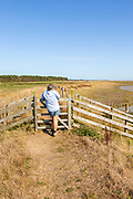Woman resting at gate on coastal footpath between River Ore and  Hollesley Marshes, Suffolk, England, UK