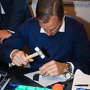 NLD/Amsterdam/20131003 -  Dad's moment ,Ronald de Boer bezig met het in elkaar zetten van een horloge