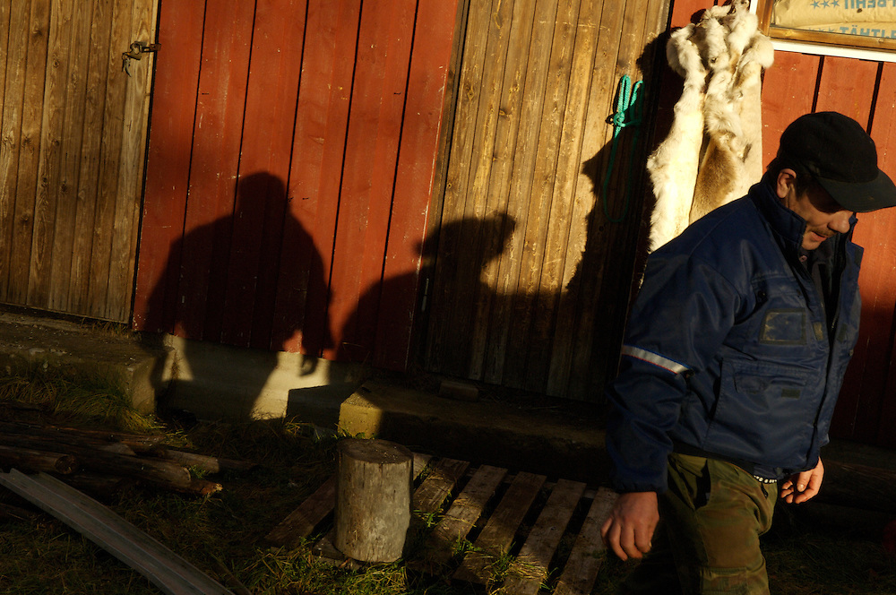 FINLAND. October 24, 2007- With trails of long shadows in the late afternoon sun, Pauli, 57, walks towards his snowmobile for repairs.