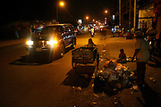 Children recycling workers collecting and scavenging for raw materials on the streets at night, Phnom Penh. Rural peasants who have left the countryside in search of earning a decent living often end up as recycling workers on Phnom Penh's city streets. They earn a few dollars a day from selling by weight the plastic bottles, aluminium cans and cardboard they collect during a days work. Usually they work from the mid afternoon until midnight, sorting through the rubbish on the streets. They take what they collect to small sorting houses on the edge of the city.