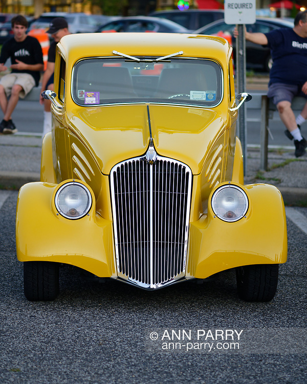 Bellmore, New York, U.S. July 30, 2021.  A classic yellow 1934 Willys 77 coupe is on display at the Bellmore Friday Night Car Show, held at the Bellmore Long Island Rail Road parking lot, with hundreds of visitors enjoying classic and customized cars and pleasant summer weather. The Chamber of Commerce of the Bellmores hosts the cruise nights each Friday from May 14 to October 1, 2021, weather permitting.
