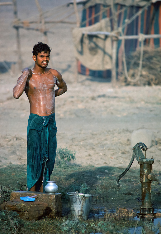 Man bathing in the street by the public water pump in India