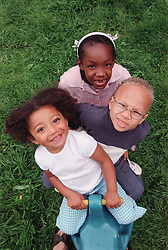 Multiracial group of children sitting on toy truck in garden,