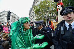 © Licensed to London News Pictures. 10/10/2019. LONDON, UK. Members of the Red and Green Brigade, supporters of Extinction Rebellion, march silently around police who have surrounded a wooden structure, which contains activists secured to it, in Trafalgar Square during day 4 of Extinction Rebellion's climate change protest in the capital.  Activists are calling on the Government to take immediate action against the negative impact of climate change.  Photo credit: Stephen Chung/LNP