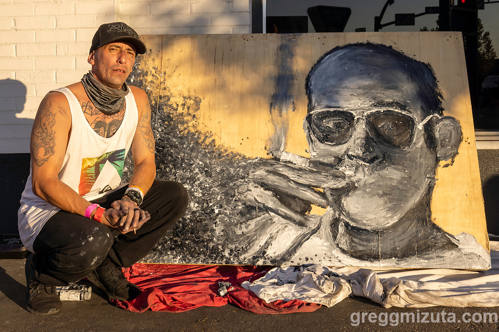 """Critter-Chris Alvarez's Artfort live painting  of Hunter S. Thompson"""" at LED in Boise, Idaho on September 25, 2021.<br /> <br /> Chris painted this portrait using his hands and fingers.<br /> <br /> Chris has been drawing most of his life and is a founding member of the art collective at Interfaith Sanctuary in Boise.<br /> <br /> He draws portraits and is a self-taught tattoo artist. Fine art and the technical aspects of drawing are what drive his creative work. He has always been interested in graffiti, and growing up in San Diego, that's what got him interested in being an artist. Graffiti was like looking at a maze with the colors and lines all over the place, and the block and bubble letters appear frequently in his work today.<br /> <br /> He draws and paints in a variety of mediums and recently completed a series of t-shirts commissioned to honor Donnie, an Interfaith Sanctuary guest who passed away in June."""