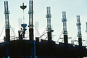 Alaska. Steelworkers help a crane with bucket of concrete for construction of a highrise building.