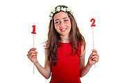 Pre-teen girl in red dress and wreath celebrates twelve