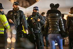 © Licensed to London News Pictures. 31/12/2018. London, UK. Armed police on The Mall watch as crowds go through a security check as they arrive to celebrate New Year's Eve in central London.  Over 100,000 people are attending London's ticketed fireworks display on the banks of the River Thames for New Year's Eve tonight. Photo credit: Peter Macdiarmid/LNP