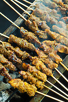 Satay or sate is a dish of marinated, skewered and grilled meat served with a side of usually peanut flavored sauce. Satay may consist of diced or sliced chicken, goat, mutton, beef, pork, fish.  The more authentic version uses skewers from the midrib of the coconut palm frond, although bamboo skewers are also often used. These are grilled or barbecued over a wood or charcoal fire, then served with various spicy seasonings. Satay originated in Java, Indonesia and is available almost anywhere in Indonesia, and other Southeast Asian countries, including Malaysia, Singapore, Brunei, and Thailand.  Satay can be found at roving satay vendors, in Southeast Asian food courts or during traditional feasts.