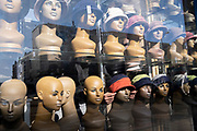 A shopkeeper fits and adjusts the hats on female mannequin heads in the window of his  hat business on the Commercial Road in the East End, on 21st October 2021, in London, England.