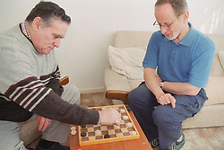 Elderly man with Alzheimer's disease playing game of draughts with day centre staff member,