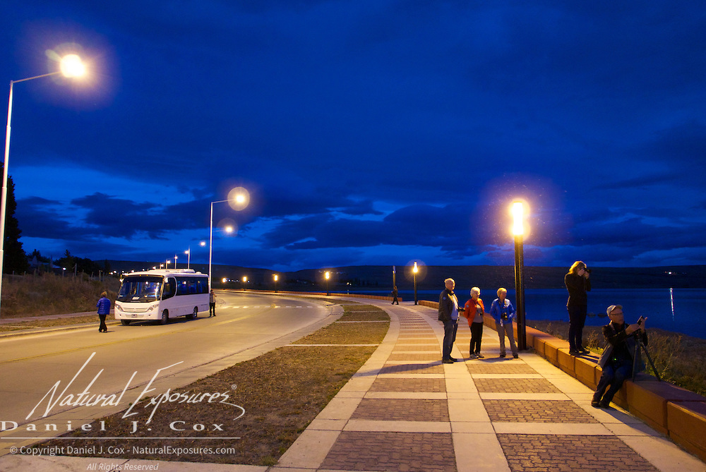 Explorers photographing the early morning light along the water front in El Calafate, Patagonia, Argentina,