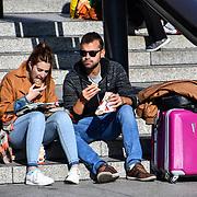 Tourists enjoy sightseers Autumn and Sunshine in Trafalgar Square, London, UK 24 October 2018
