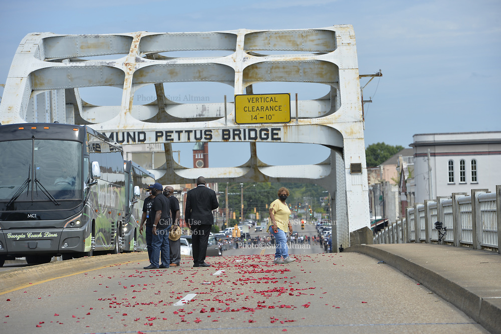 7/26/2020 SELMA/Alabama - John Lewis's family is seen walking on the Edmund Pettus Bridge moments before they walk  behind the casket over the Edmund Petus Bridge, and then once over they are seen placing roses on the casket. The United States honor Guard carry the casket of Civil Rights Icon and Congressmen John Lewis from the horse the horse drawn carriage that just crossed the Edmund Pettus Bridge for the last time into the casket to head to the State Capitol, where he will lay in state.. A horse drawn carriage from Watkins Funeral Home in Atlanta leads the flag draped casket of Civil Rights icon and Congressman John Lewis over the Edmund Pettus Bridge for the last time.The rose petals represent the blood shed from Bloody Sunday in 1965 where Lewis was beaten by police and ended up with a  fractured skull. On the anniversary of President Lyndon Johnson signing the Voting Rights Act, Congressman John Lewis's casket is pulled by a horse drawn carriage  across the Edmund Pettus Bridge in Selma for the last time. The casket is headed to the State Capitol in Montgomery where he will lay in state and then will head to Washington DC and then to his final resting place in Atlanta Georgia.  Photo© Suzi Altman