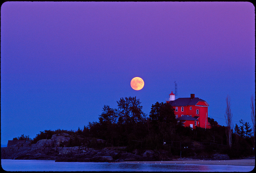 THE MARQUETTE LIGHTHOUSE ON LAKE SUPERIOR WITH FULL MOON IN MARQUETTE MICHIGAN.