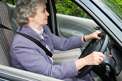 Older woman driving a car along the road,
