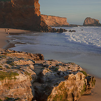 A couple takes pictures under the colorful, eroded cliffs at Panther Beach, north of Santa Cruz, California