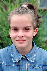 Portrait of young girl with hair in ponytail smiling,