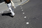 A lady wearing trousers with a dotted pattern crosses the road in the City of London, the capitals ancient, financial district, on 14th May, in London, England.