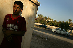 Havdar Fareed, 14, who sells refreshments along the road, is seen in Baghdad, Iraq, July 23, 2003. With two brothers who were Fedayeen before the war, Fareed was trained by the Saddam Hussein regime in a military camp so he could also become a Fedayeen fighter.